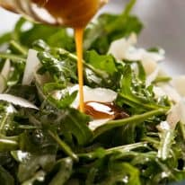 Close up of Balsamic Dressing being drizzled over rocket salad with shaved parmesan