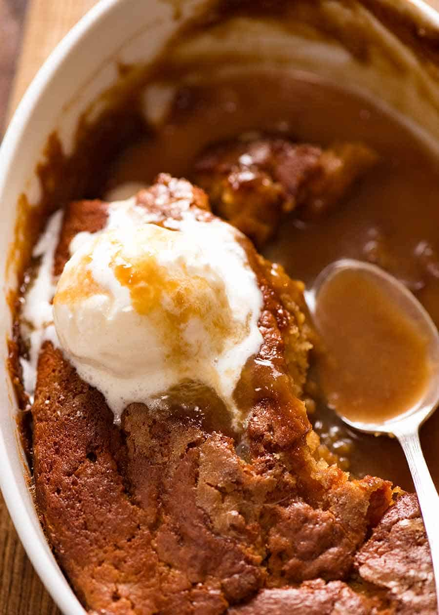 Close up of Self Saucing Butterscotch Pudding in baking dish, being served