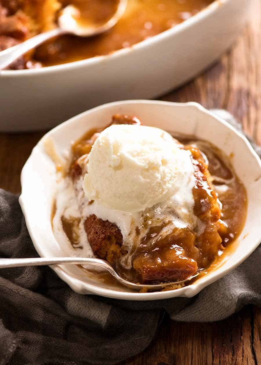 Butterscotch Pudding (Self Saucing) in a bowl with ice cream, ready to be eaten