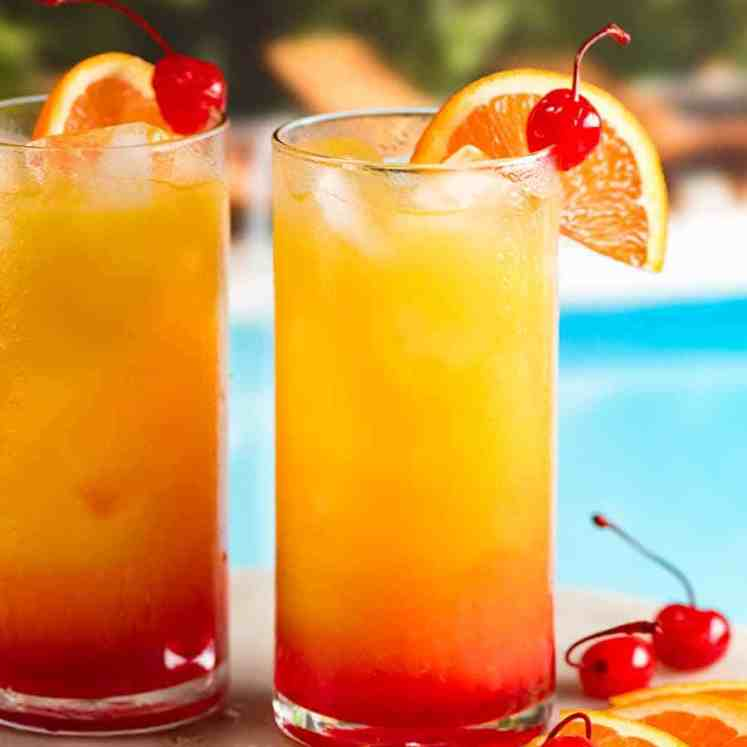 Two Tequila Sunrise cocktails by a pool, garnished with orange slice and maraschino cherries ready to drink