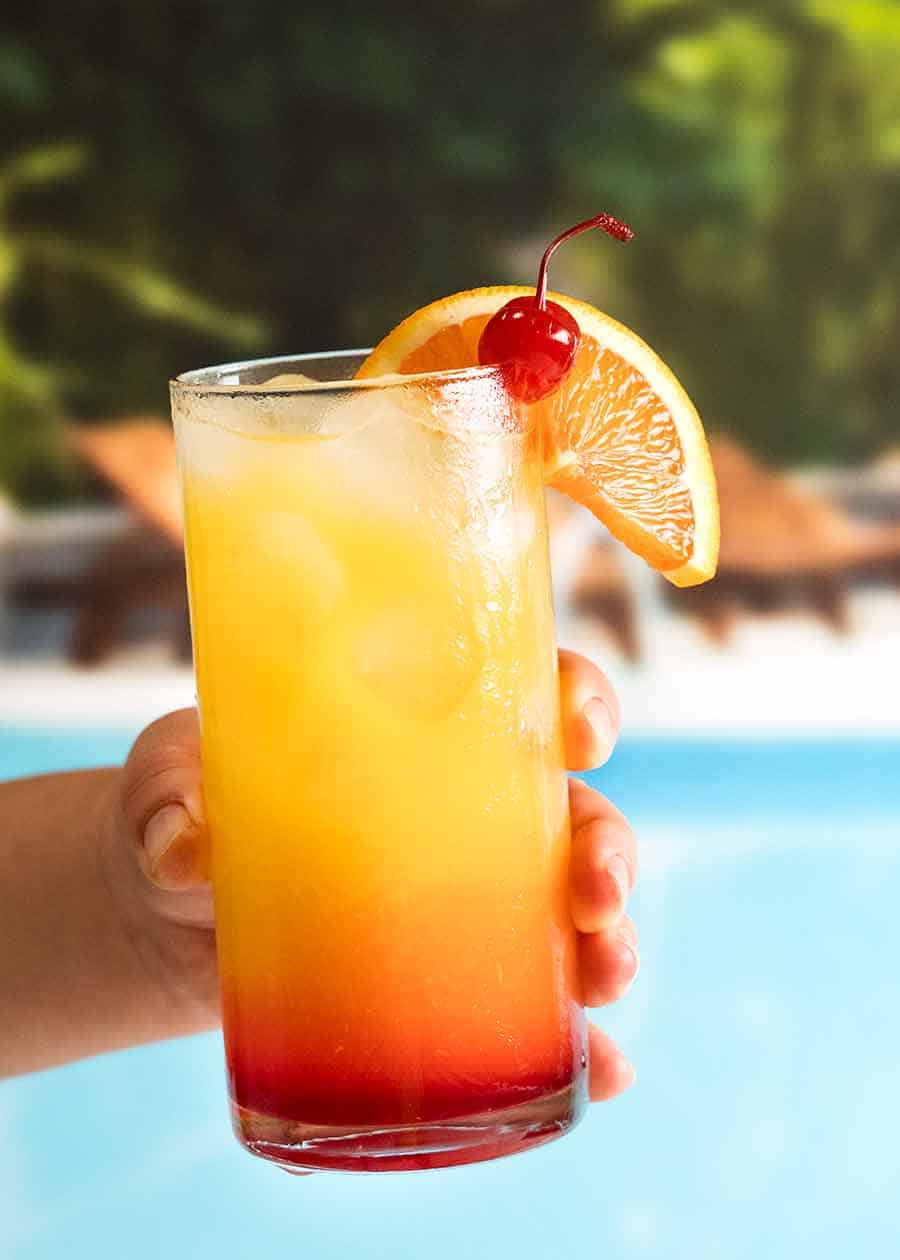 Hand holding Tequila Sunrise by a pool