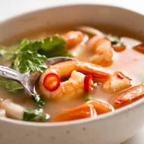 White bowl with Tom Yum Soup (Thai soup) with prawns / shrimp, mushrooms, tomato and garnished with coriander and chilli