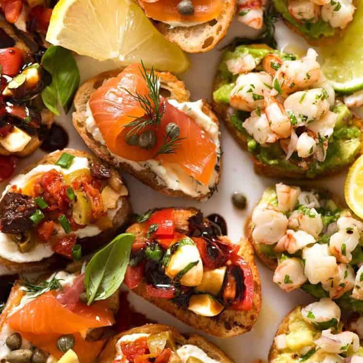Serving platter filled with Crostini - Smoked Salmon, Shrimp Avocado, Mediterranean and Caprese