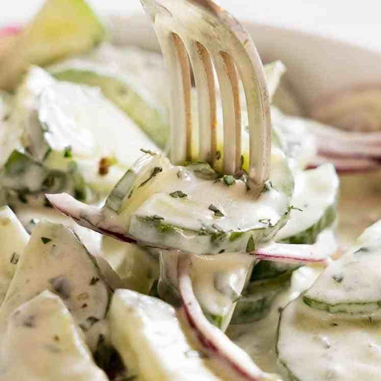 Close up of fork picking up Cucumber Salad with Lemon Mint Yogurt Dressing