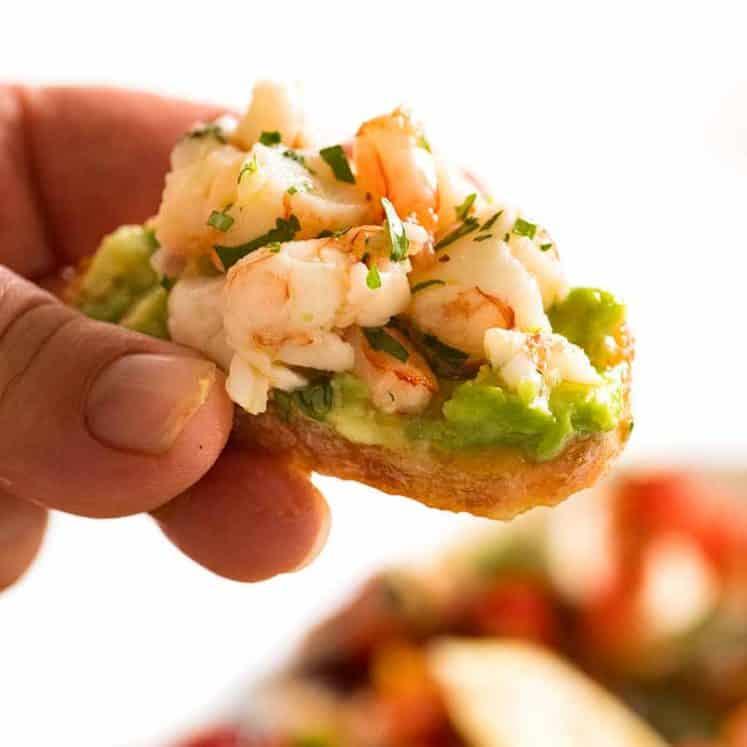 Close up of Prawn/Shrimp Avocado Crostini held by hand