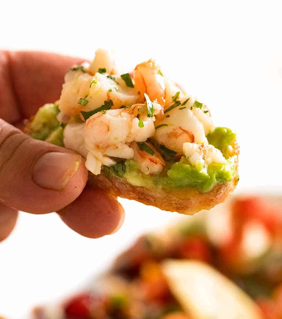 Close up of Prawn/Shrimp Avocado Crostini held by hand