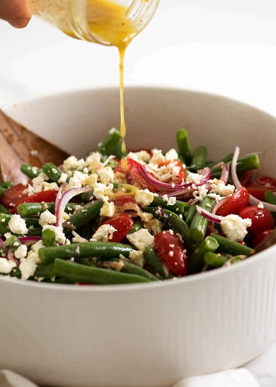Drizzling lemon dressing over Green Bean Salad with Cherry Tomatoes and Feta