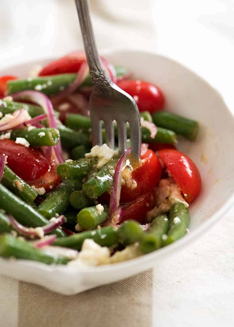 Close up of forkful of Green Bean Salad with Cherry Tomatoes and Feta