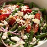 Close up of Green Bean Salad with Cherry Tomatoes and Feta in a white salad bowl, ready to be served