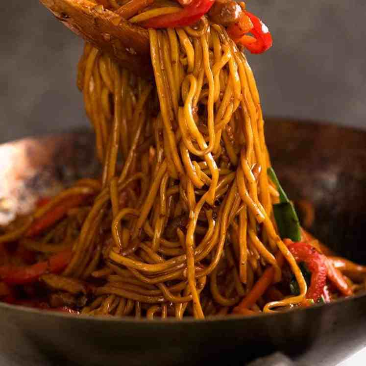 Tossing Lo Mein noodles in a wok