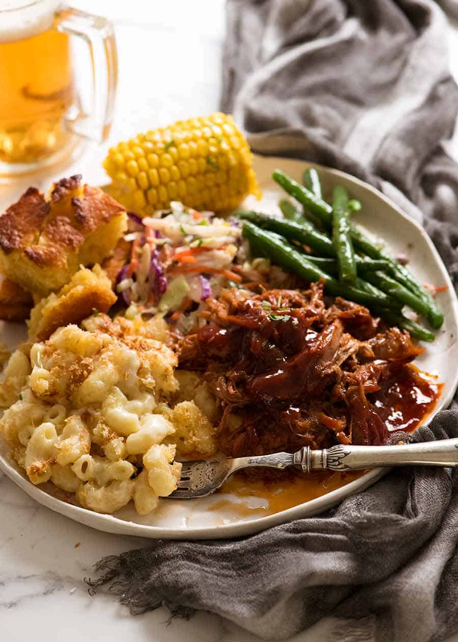Dinner plate with Pulled pork with BBQ Sauce with side dishes - Mac and Cheese, steamed greens, cornbread and steamed corn