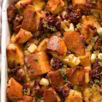 Close up of Sausage Stuffing recipe in a white baking dish, fresh out of the oven ready to be served