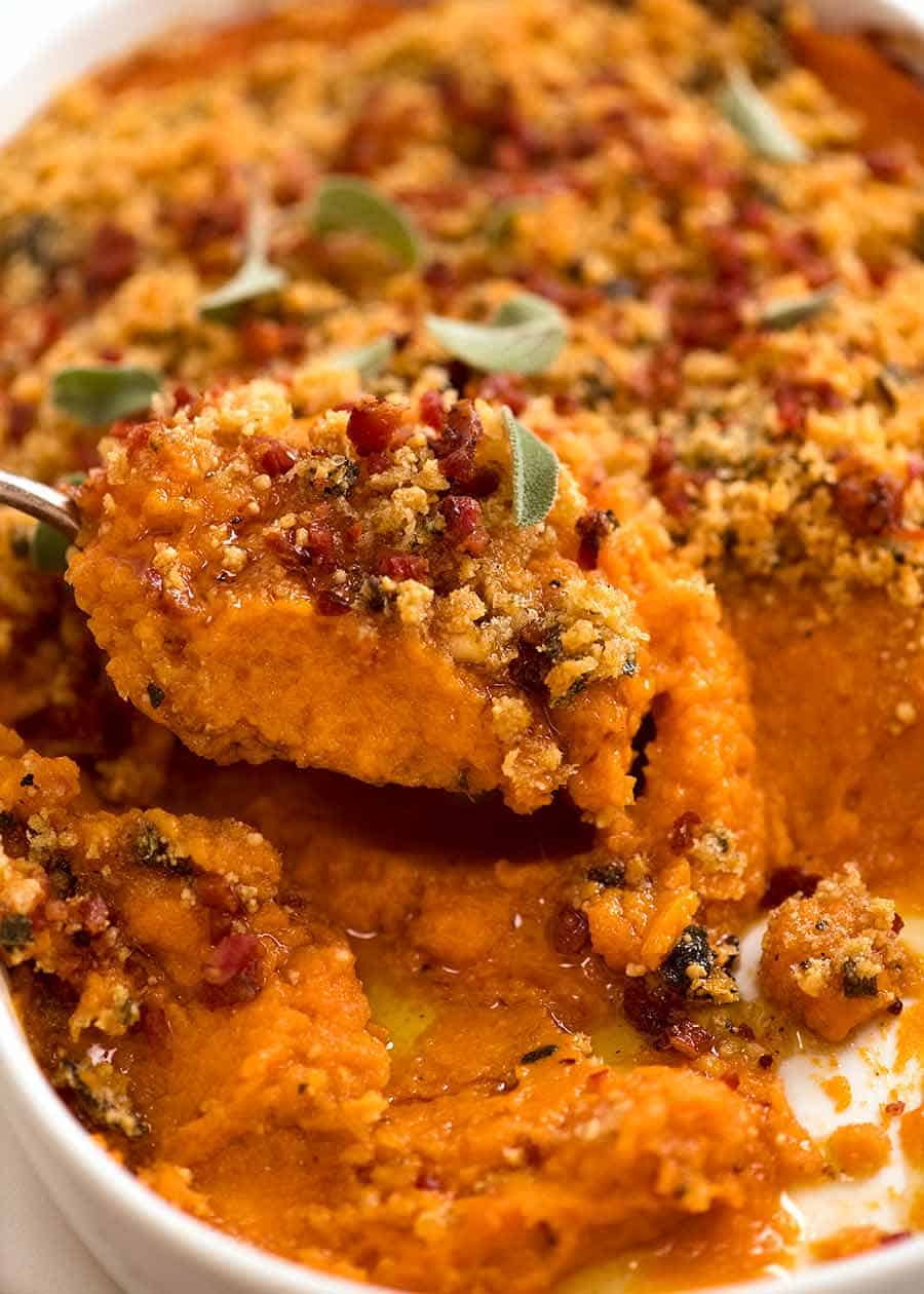 Close up of spoon scooping Browned Butter Sweet Potato Casserole from baking dish