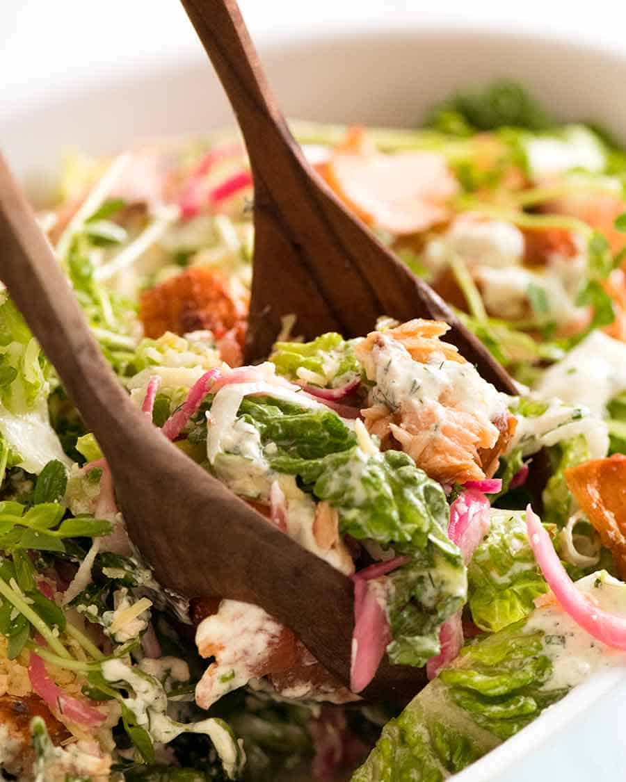 Close up of salad servers picking up Celebration Salmon Salad (salad main dish with salmon)