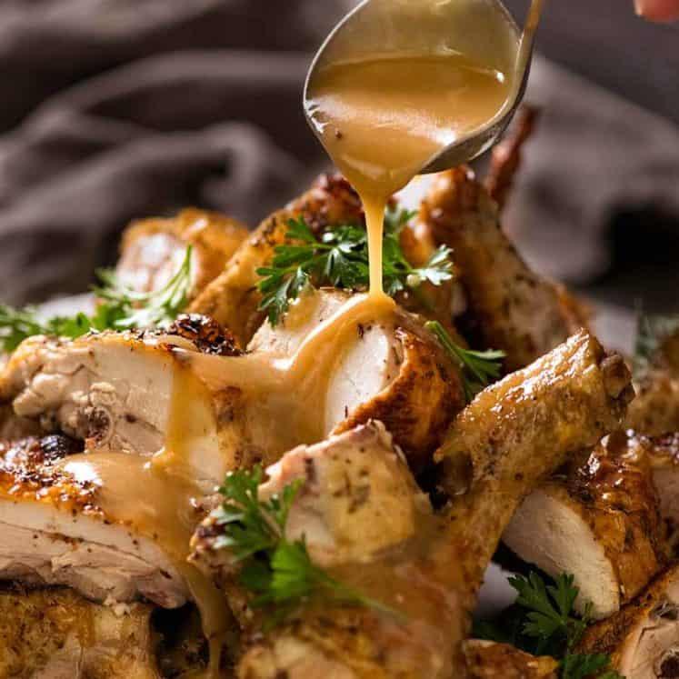 Pouring gravy over roast chicken