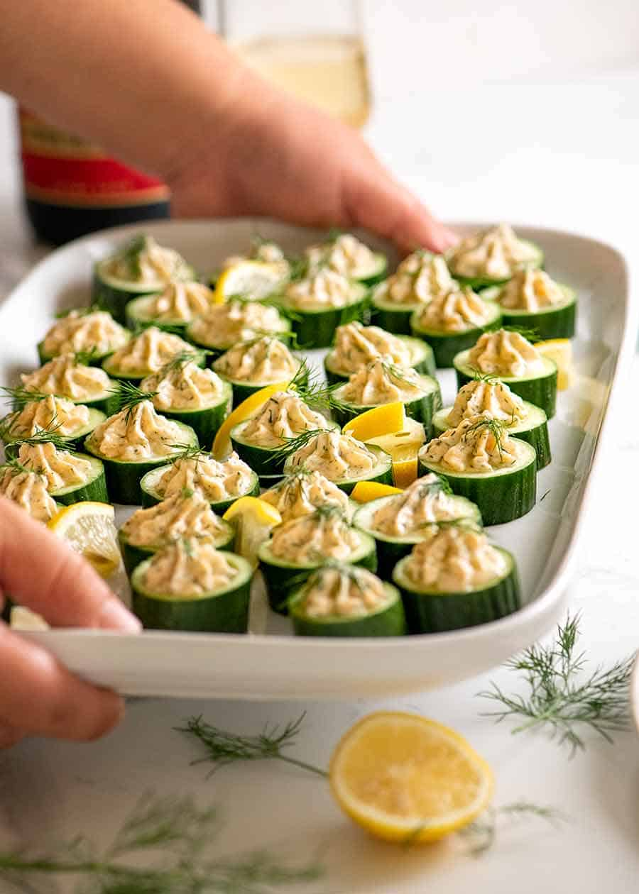 Platter of cucumber appetisers topped with smoked salmon mousse