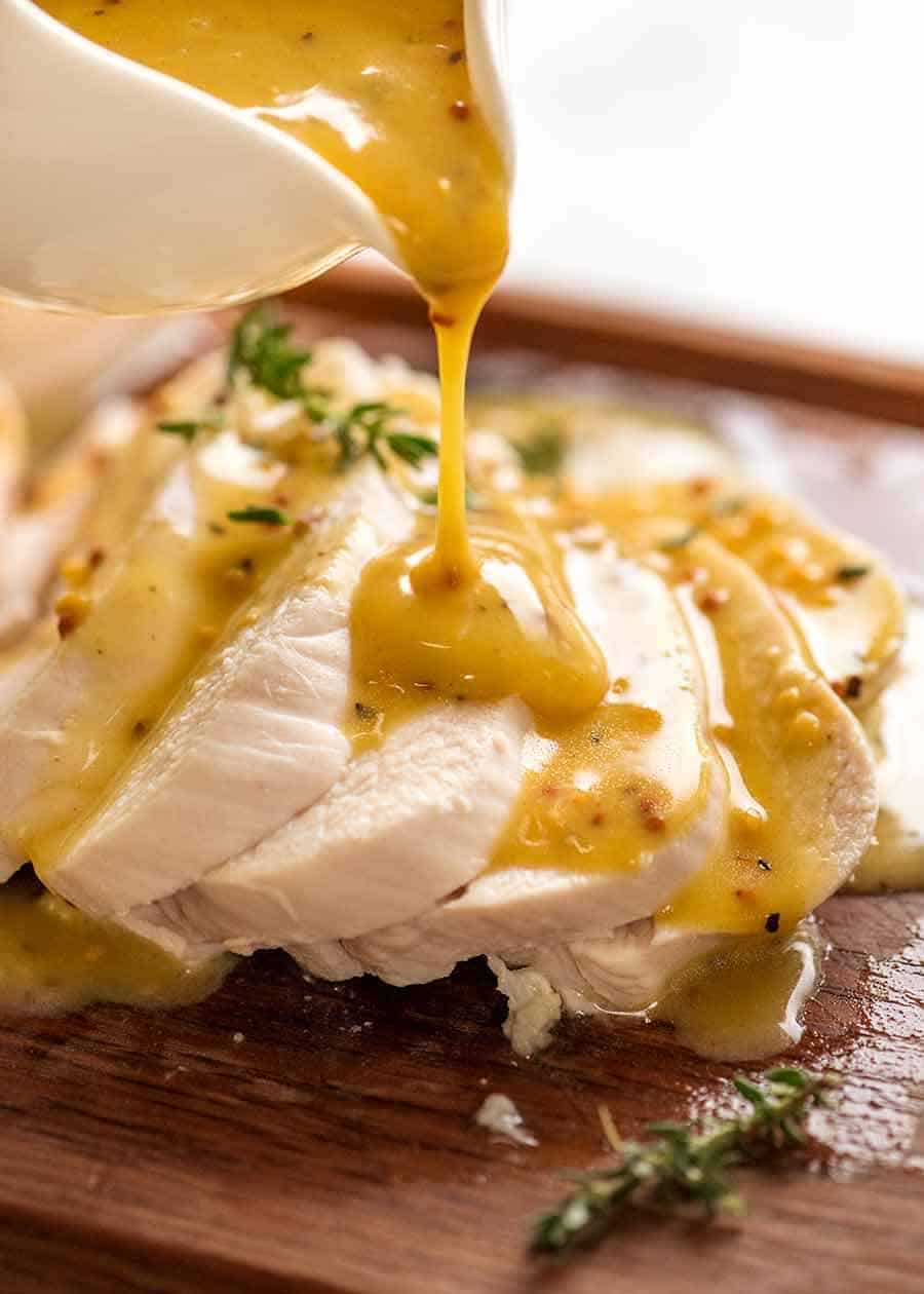 Pouring honey mustard sauce over perfectly poached chicken