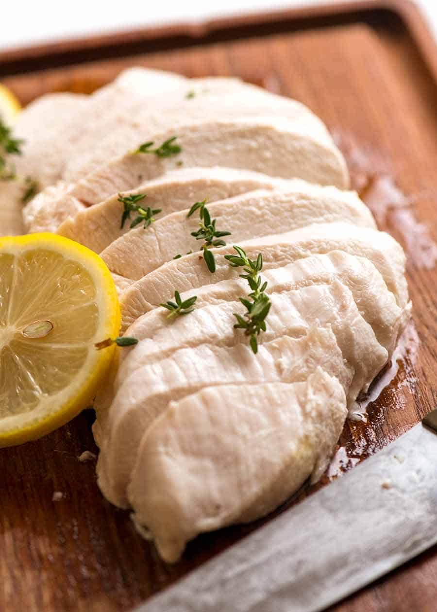 Sliced Poached Chicken breast on a cutting board