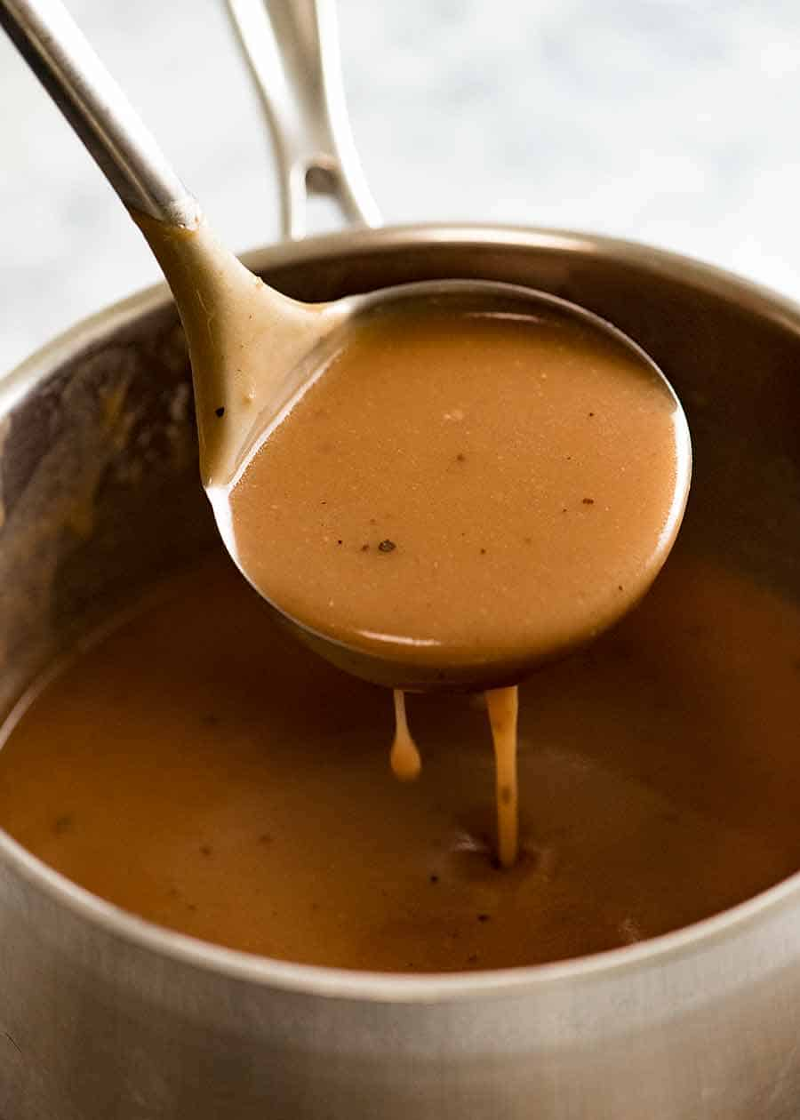 Ladle scooping up gravy from saucepan