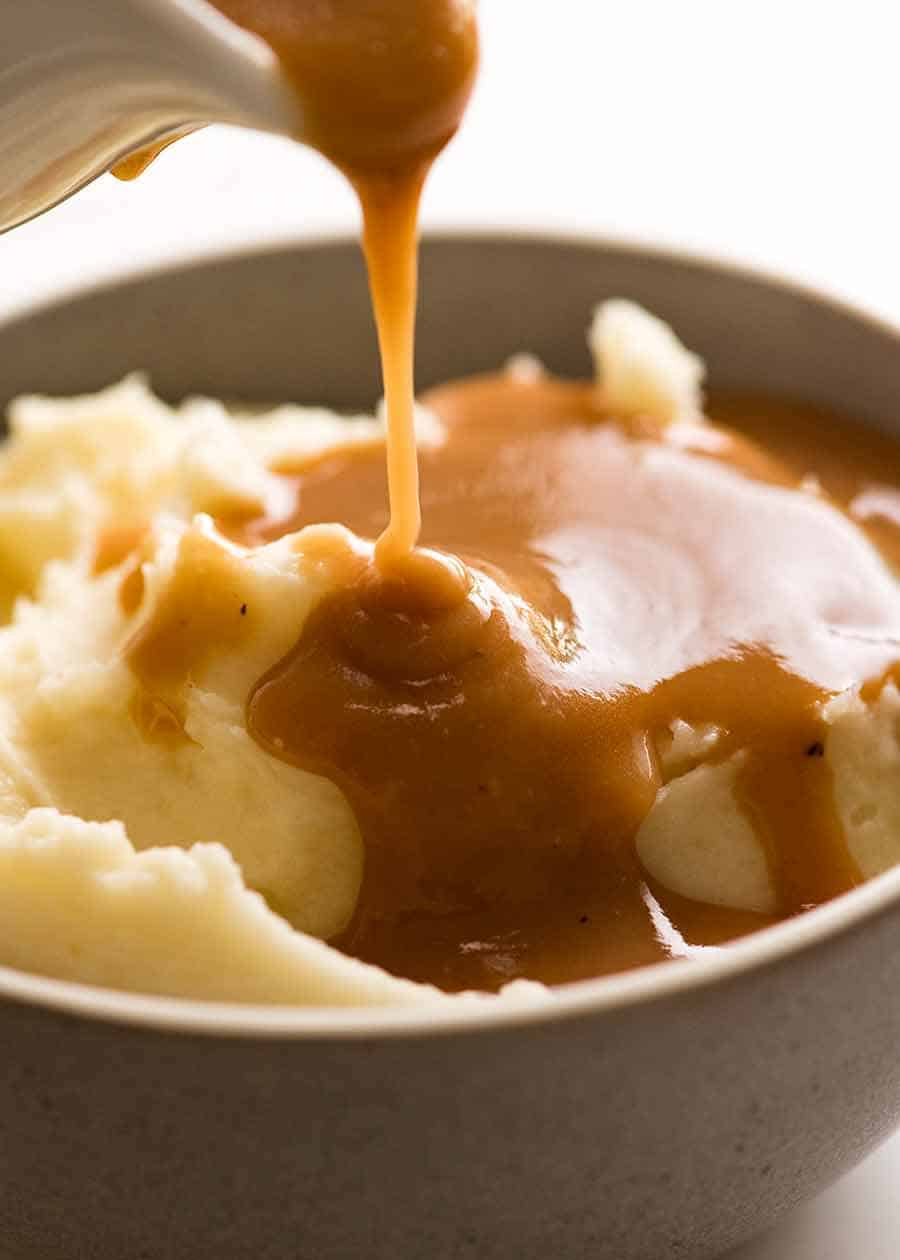 Pouring gravy over mashed potato