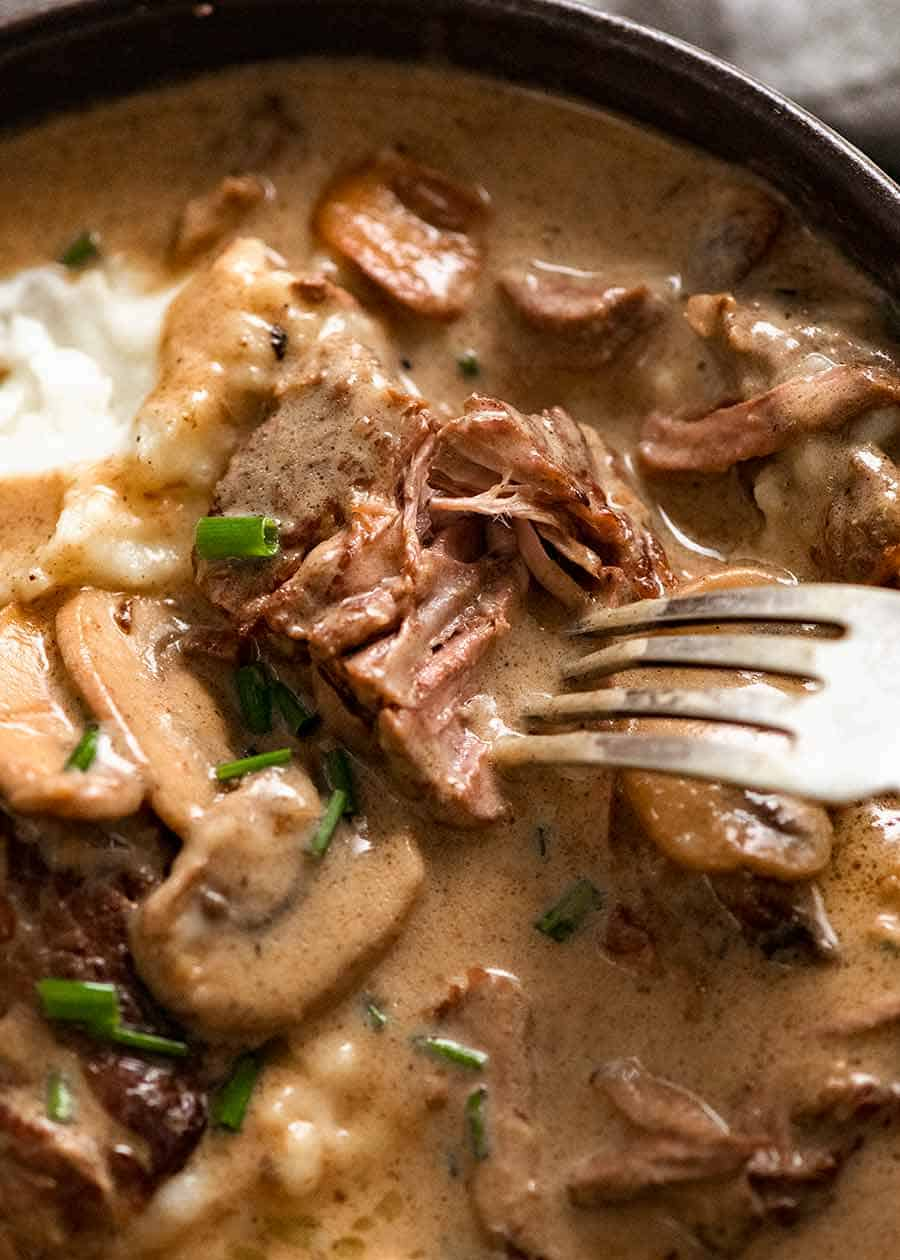 Close up showing fall apart slow cooked beef smothered din Beef Stroganoff sauce