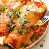 Plate of juicy Chicken Enchiladas, ready to be devoured