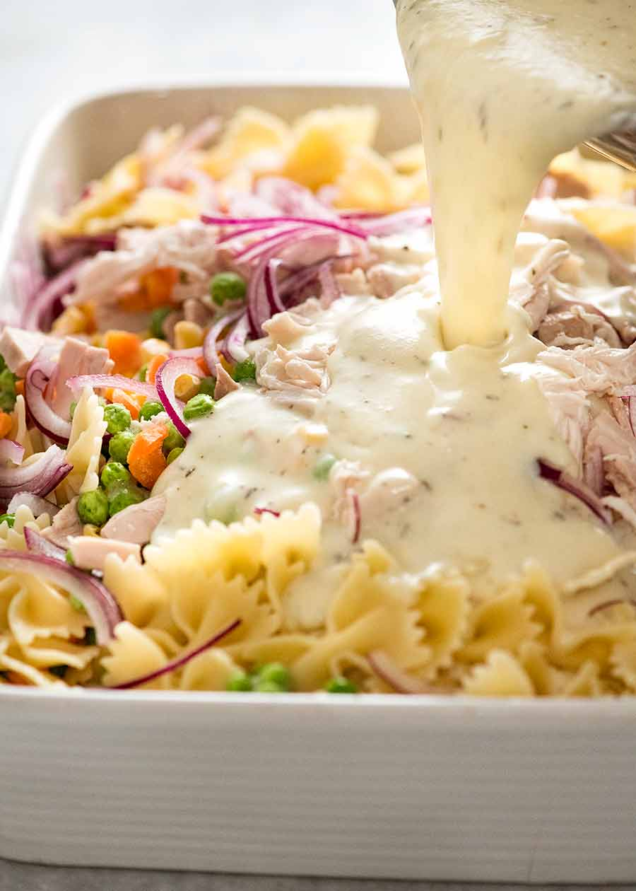 Pouring creamy sauce over pasta, chicken and vegetables