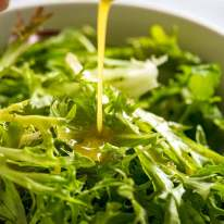 Pouring salad dressing over leafy salad