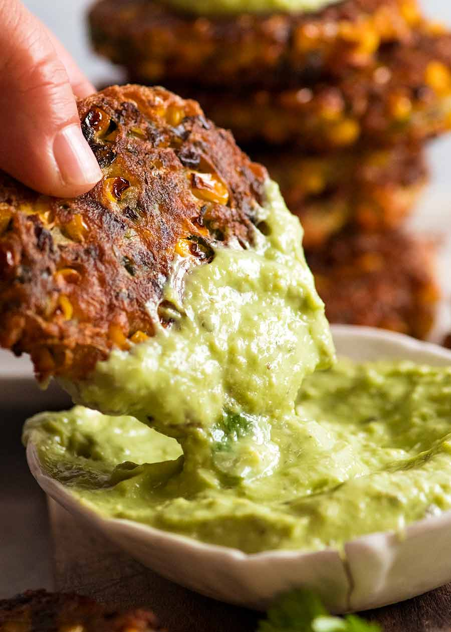 Hand dipping Crispy Corn Fritters into avocado sauce