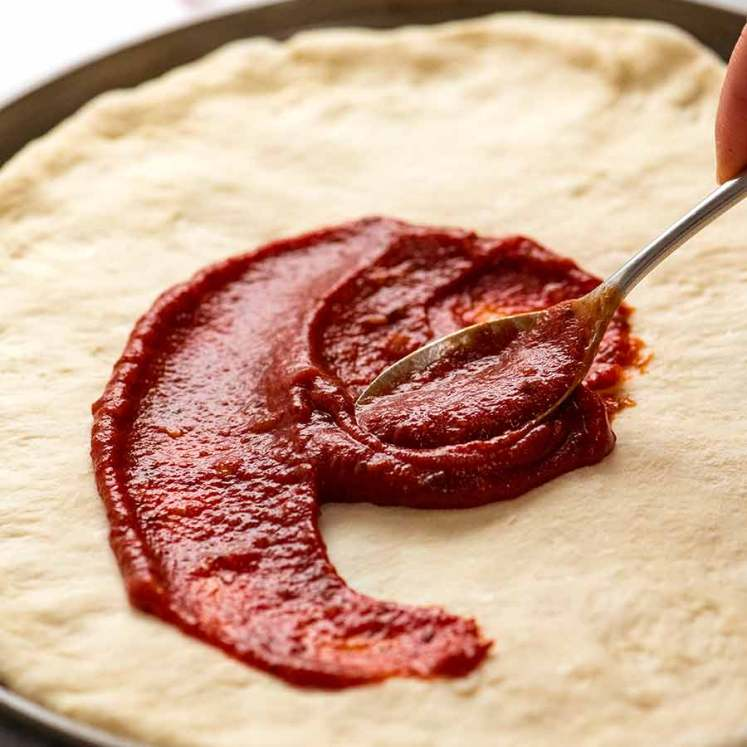 Spreading pizza sauce on homemade pizza crust