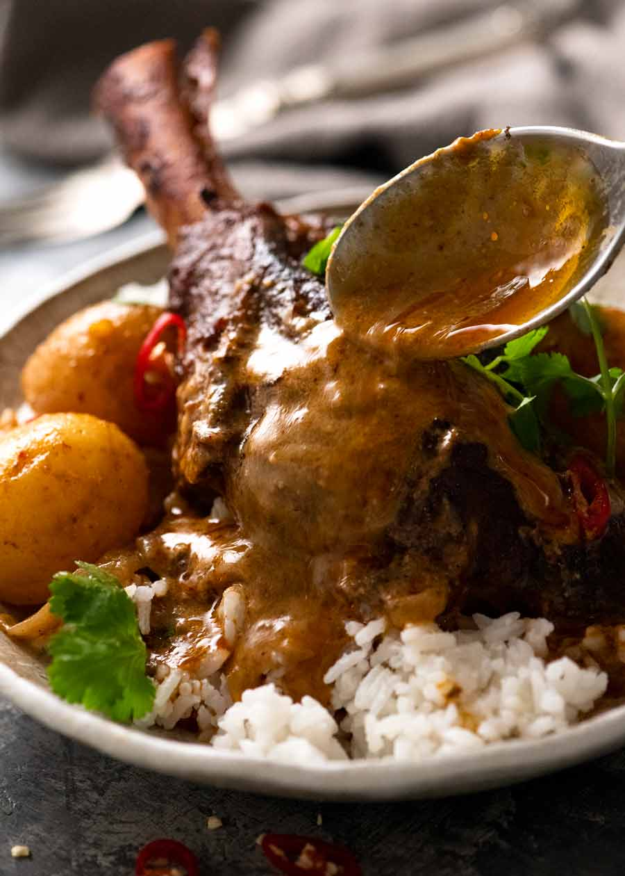 Pouring Massaman Curry over slow cooked lamb shanks