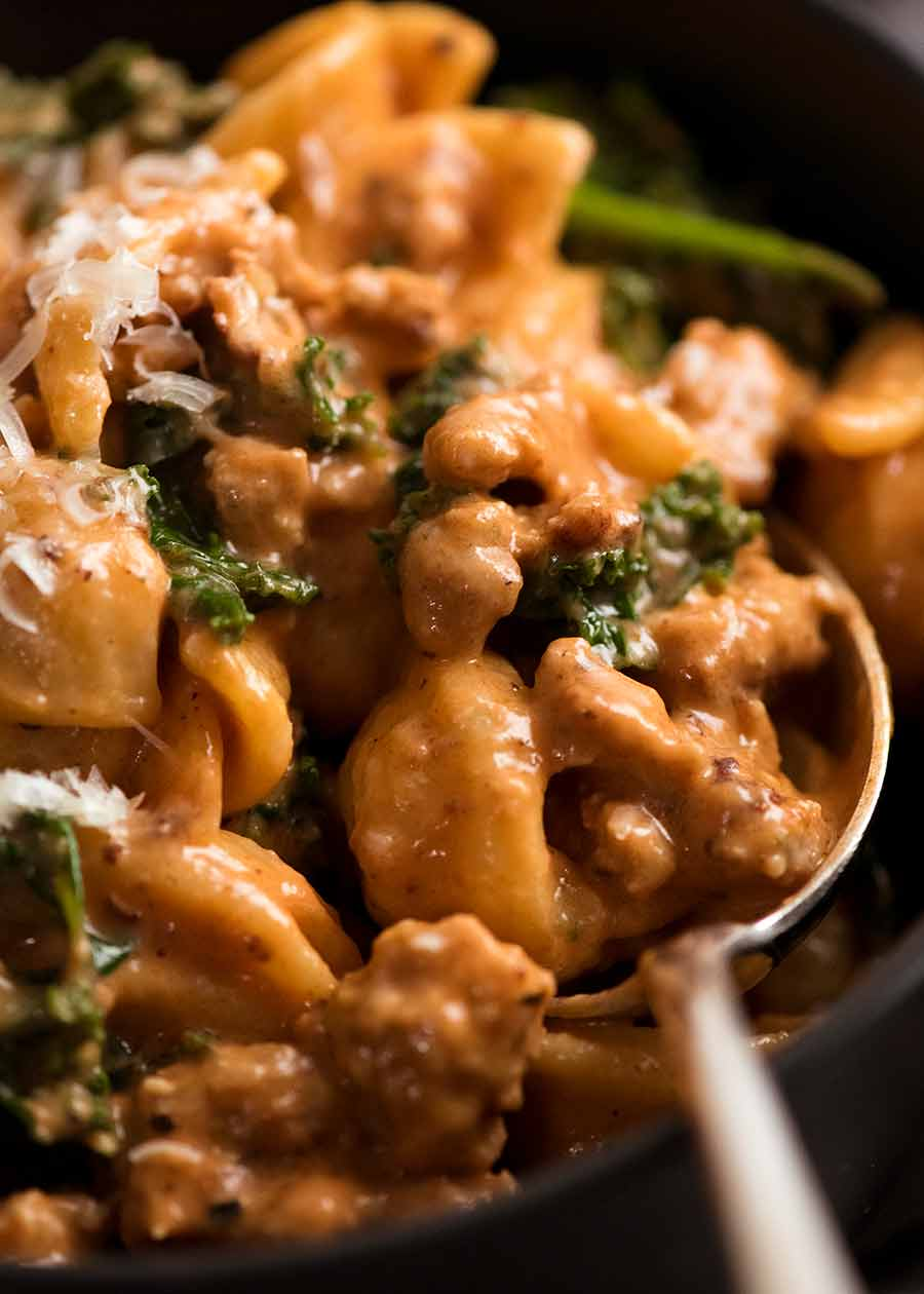 Close up of spoon scooping up Orecchiette Sausage Pasta in Creamy Tomato Sauce