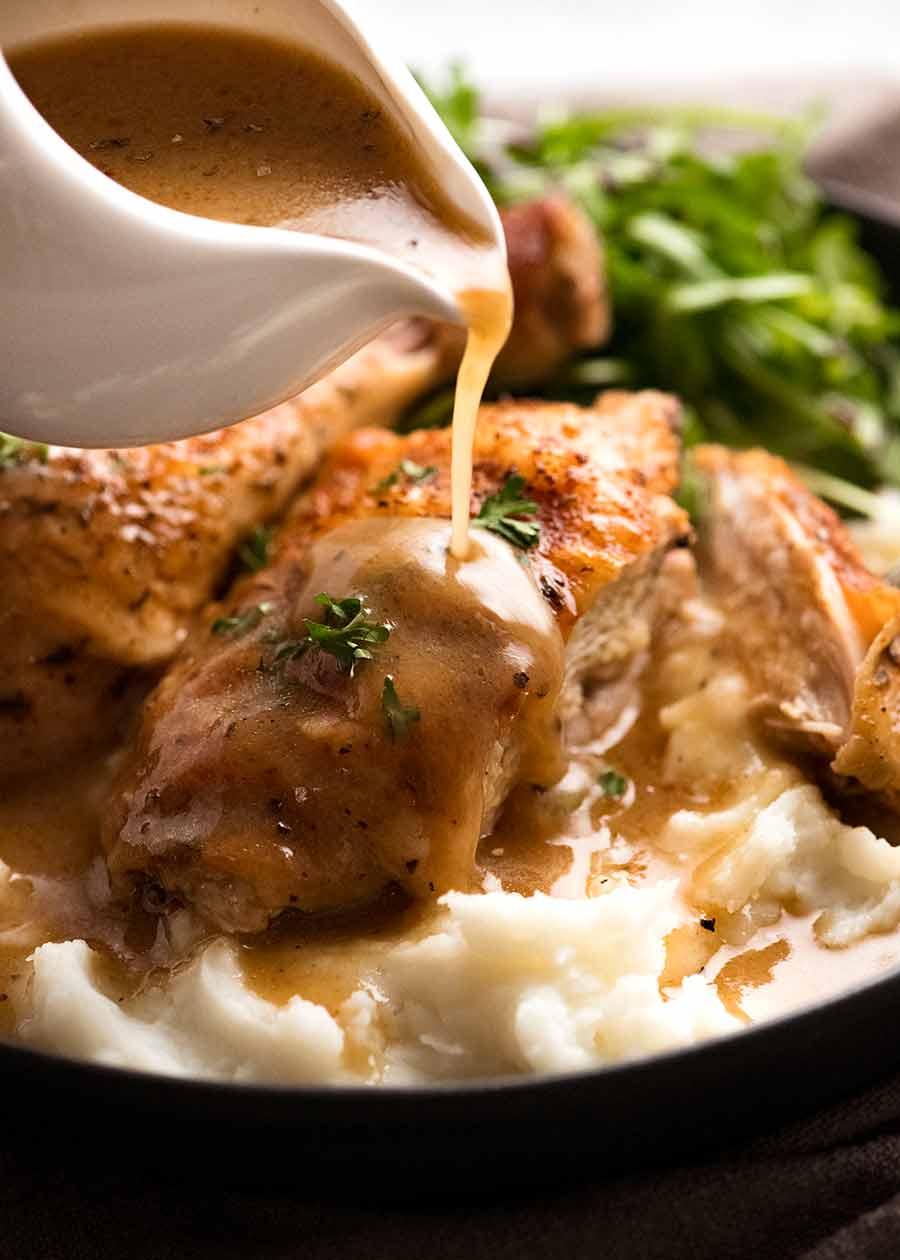 Pouring gravy over crispy baked chicken