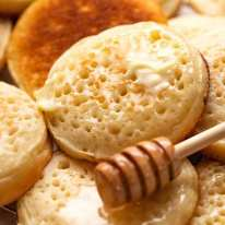 Close up of homemade crumpets with honey and butter