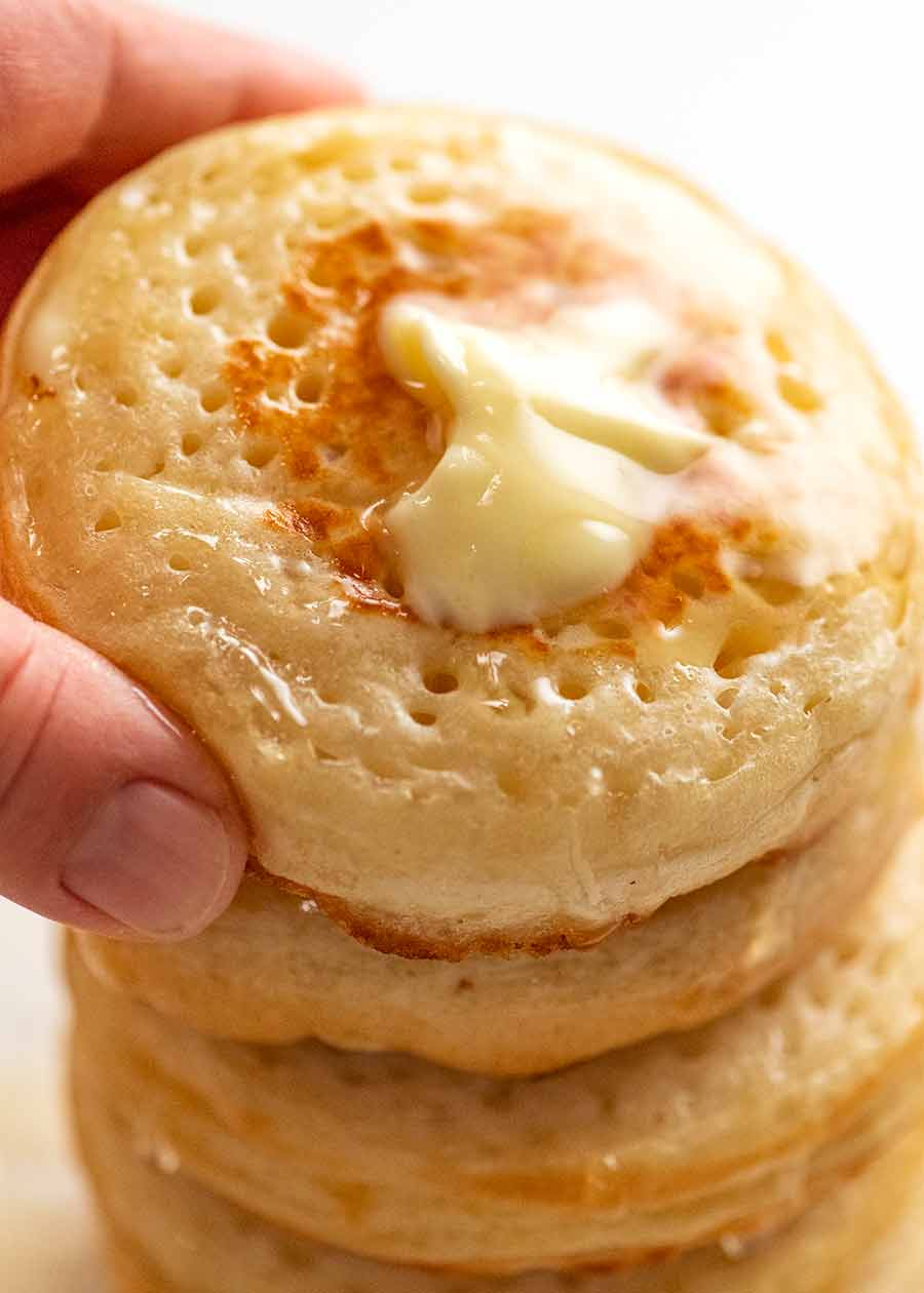 Hand picking up homemade crumpets