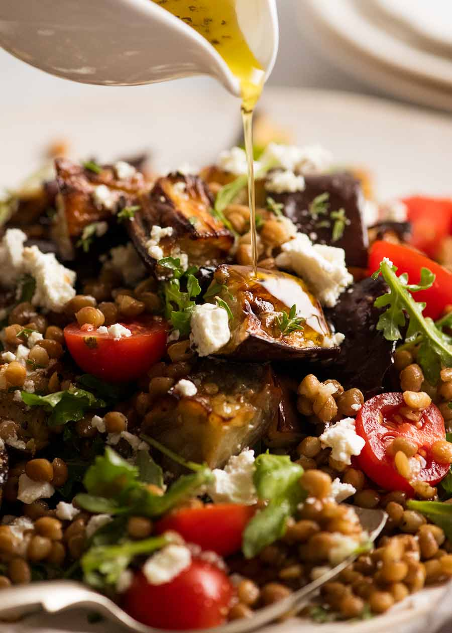 Drizzling lemon dressing over Roasted Eggplant Lentil Salad