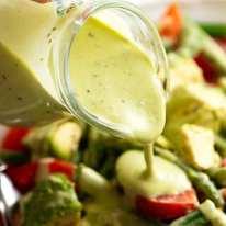 Pouring Creamy Avocado Dressing over green bean salad