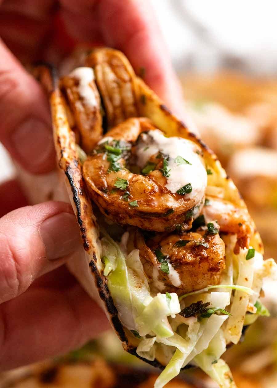 Hand holding prawn taco