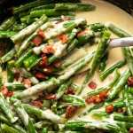 Close up photo of Green beans in creamy parmesan sauce with bacon