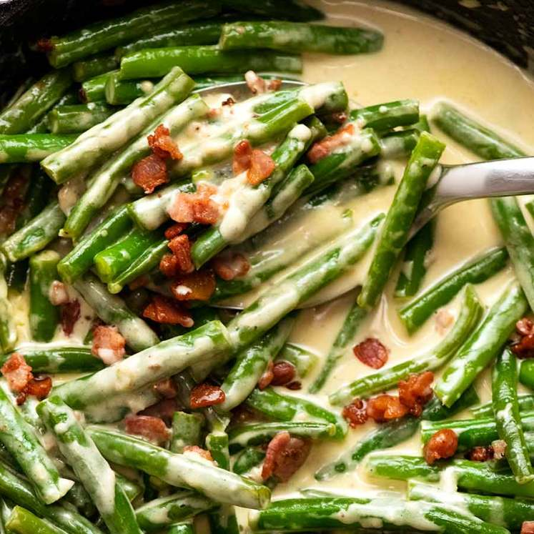 Close up overhead photo of Green beans in creamy parmesan sauce with bacon, fresh off the stove ready to be served
