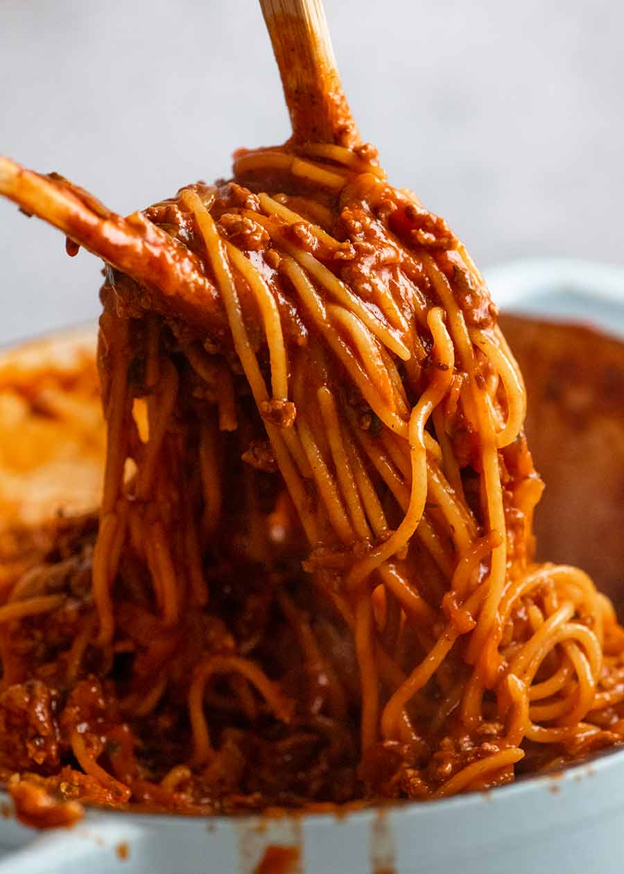 Using two wooden spoons to serve One Pot Pasta Bolognese