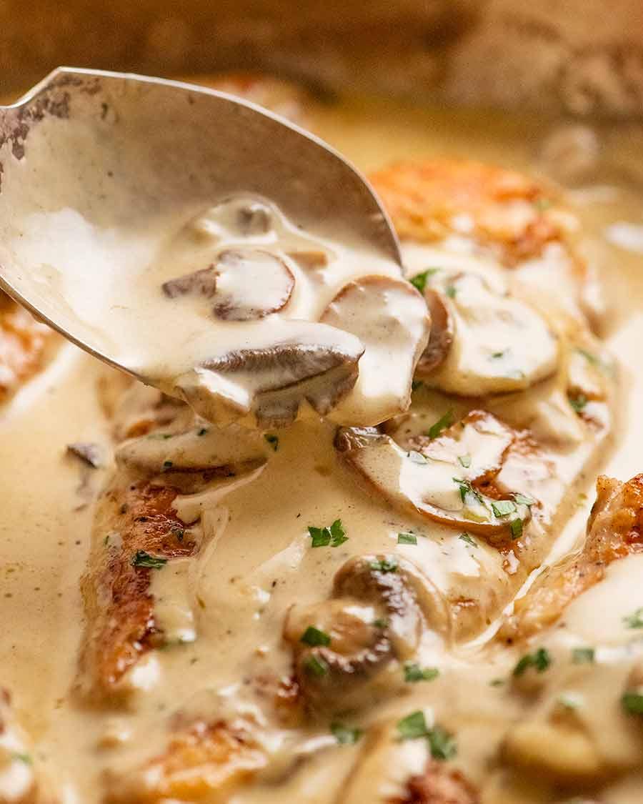 Colher molho cremoso de cogumelos sobre peito de frango