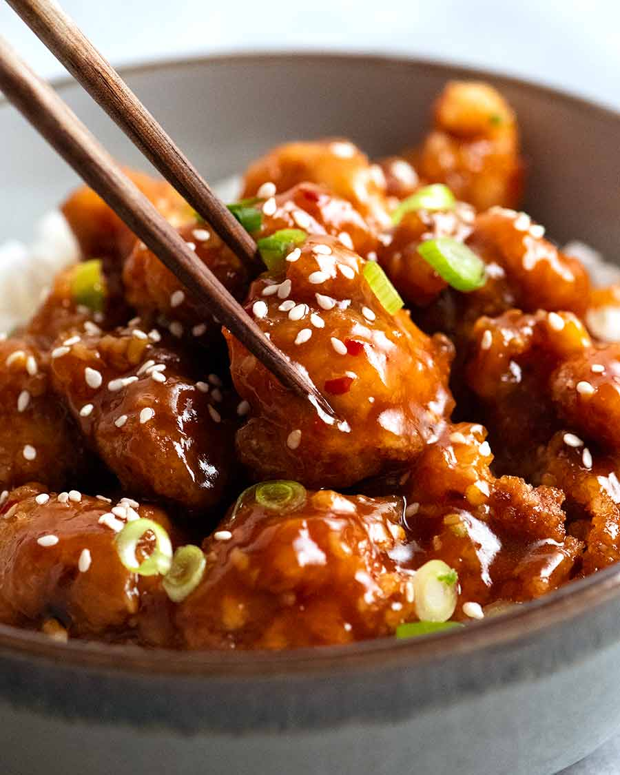 Close up of chopsticks picking up a piece of General Tso's Chicken
