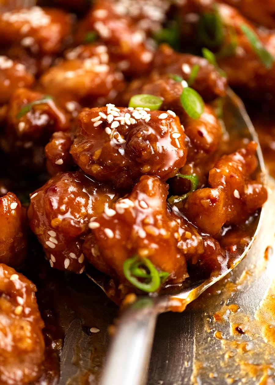 Spoon scooping up General Tso's Chicken from a skillet