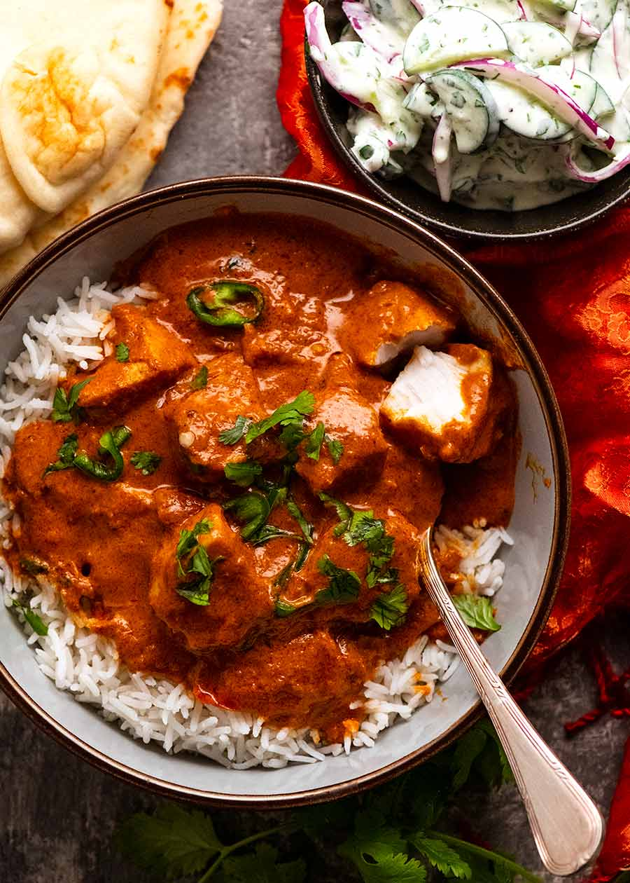 Overhead photo of Goan Fish Curry served in a bowl with basmati rice with a side of cucumber yogurt salad and naan