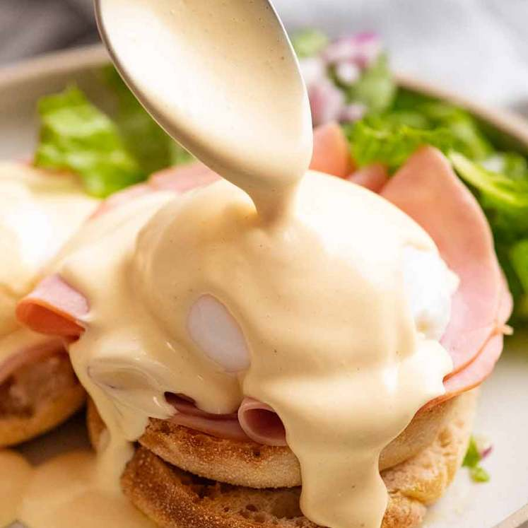 Pouring Hollandaise Sauce over Eggs Benedict