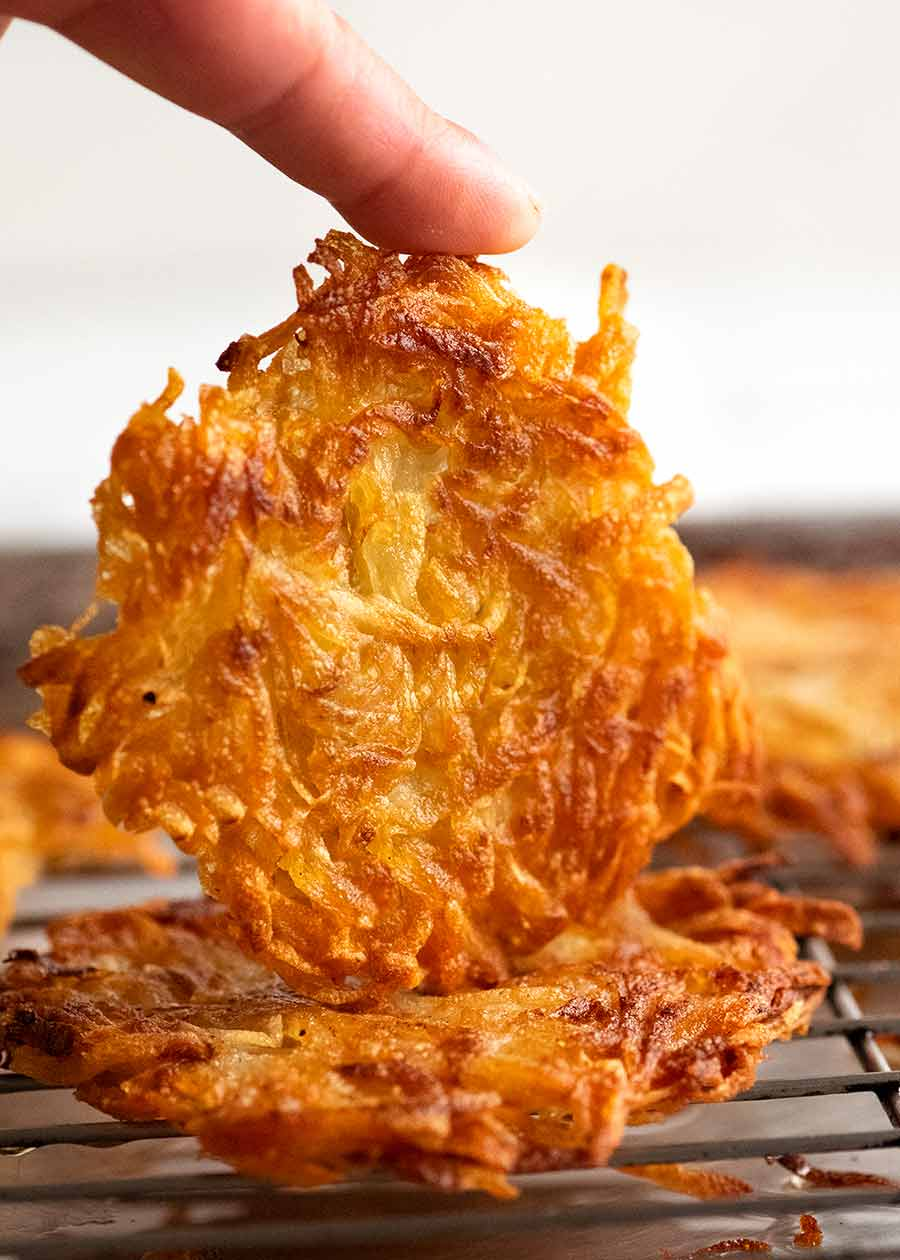 Finger holding Potato rosti on side to show how crispy it is