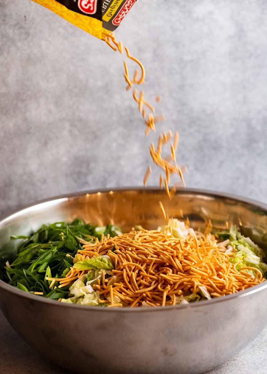 Scattering crispy noodles over crispy noodle salad