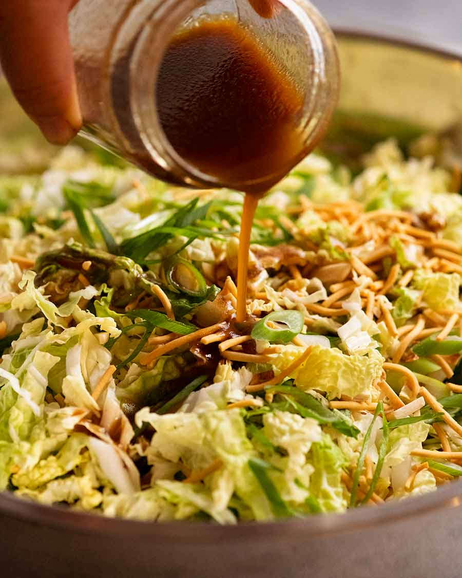 Pouring dressing over Chang's Crispy Noodle Salad