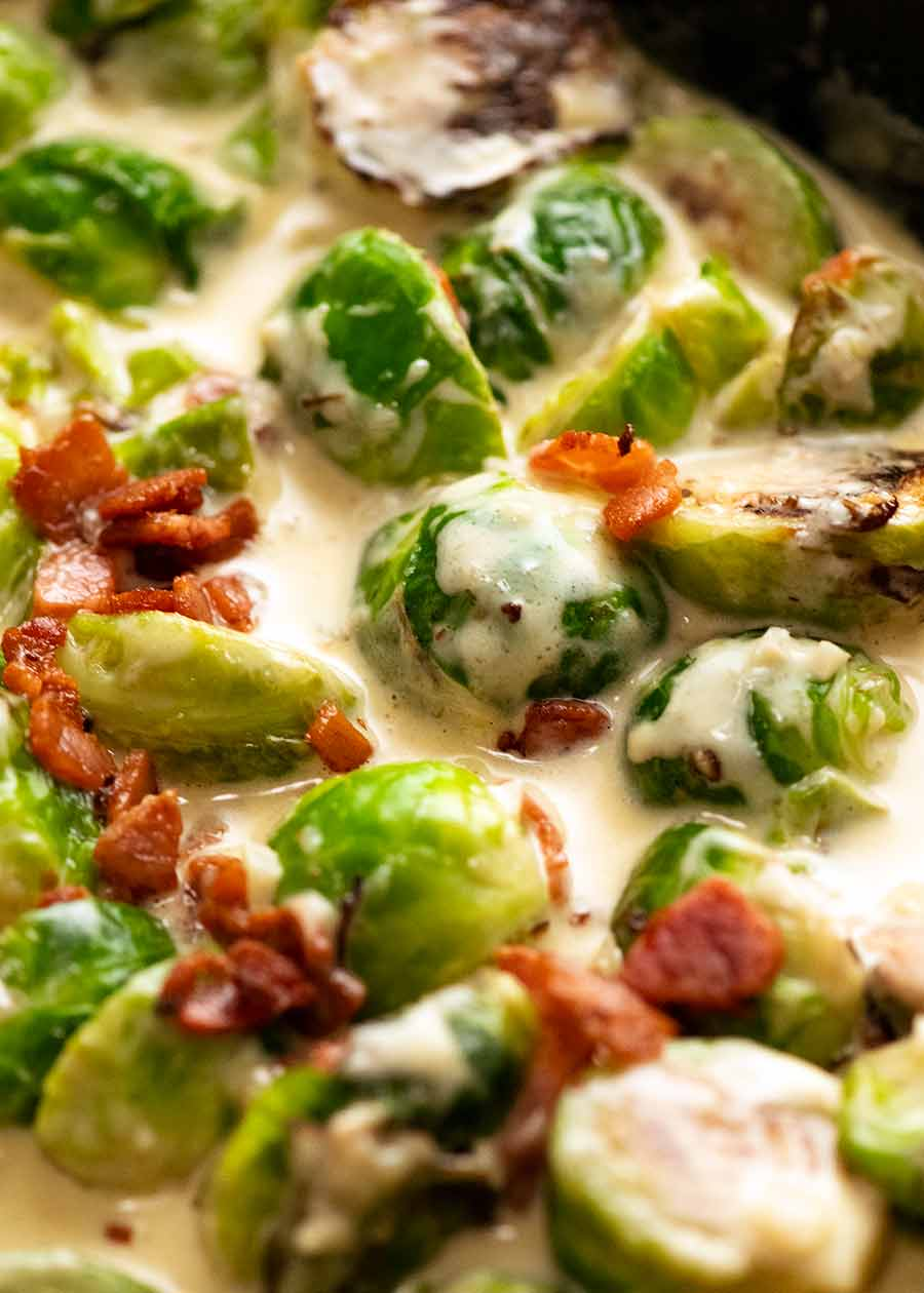 Close up of Brussels Sprouts in a creamy sauce with bacon in a skillet